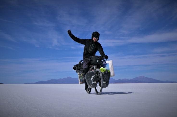 Homme à vélo dans un désert de sel