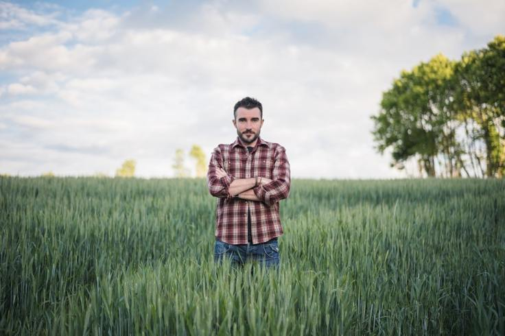 Agriculteur avec les bras croisés dans son champs en Bretagne