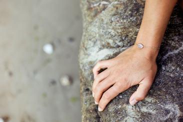 Main portant un bracelet des bijoux Arméria sur une plage bretonne