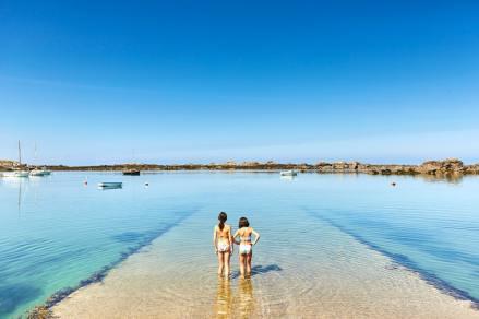 Deux filles les pieds dans l'eau sur une digue en Bretagne