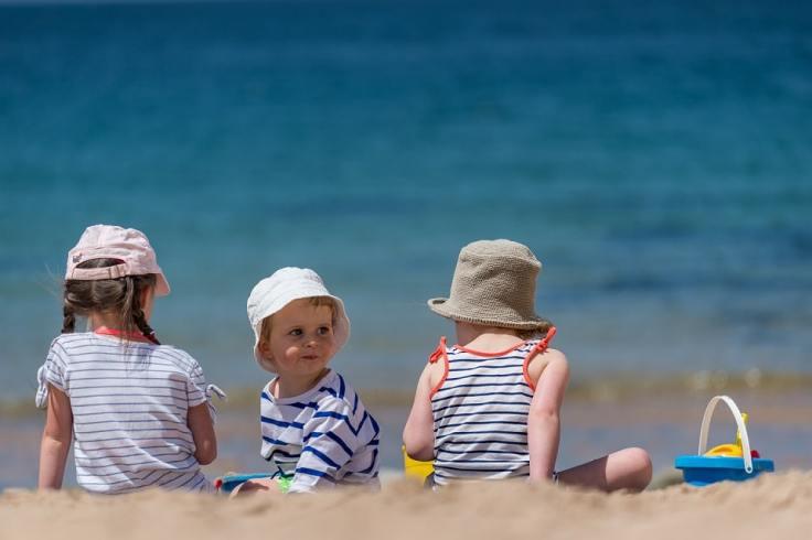 Trois enfants qui jouent sur la plage avec une marinière
