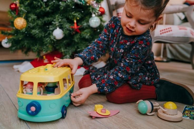 Jeune garçon qui découvre son nouveau jouet au pied du sapin