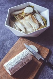 Endives cuites dans un plat et fromage de chèvre découpé sur planche de bois.