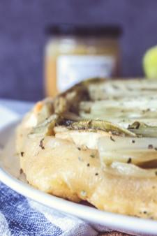Zoom sur un coin de la tarte tatin d'endives : pâte, endives, fromage de chèvre.