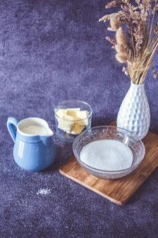 Du sucre, du lait et du beurre salé posés sur une table