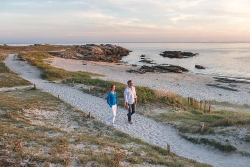 Couple se baladant sur un sentier de sable en bord de mer à Quiberon