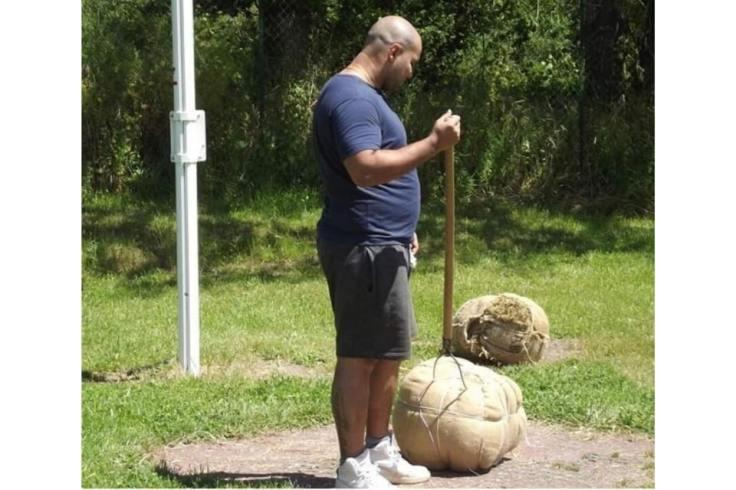 Un homme s'apprête à jouer au jeu breton vintage du lancer de botte de paille avec une fourche