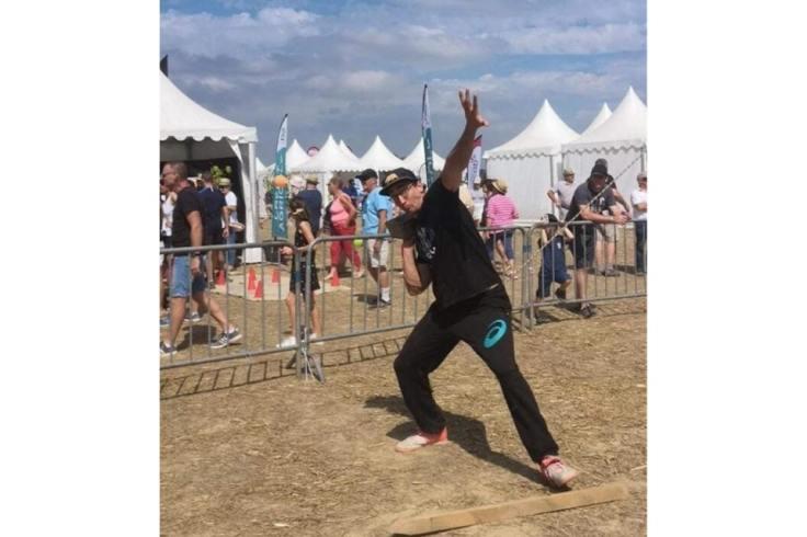 Un homme s'apprête à lancer un poids, c'est le jeu breton vintage du lancer de poids.