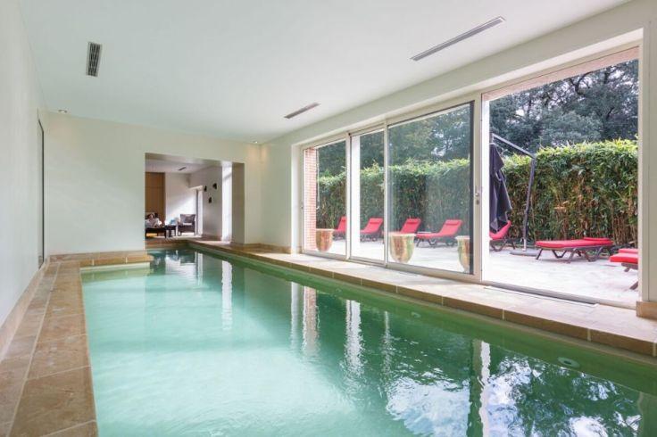Une piscine d'intérieur avec des transats autour pour se détendre dans le spa de la Bretesche