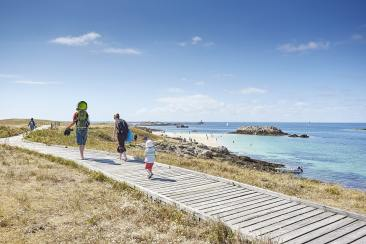 Une famille marche sur la promenade au bord de l'eau