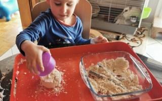 Samuel fait du sable magique avec un moule.