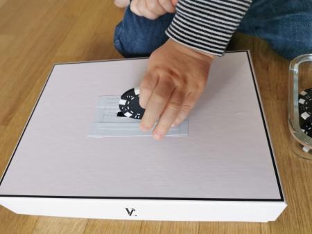 Un enfant insère un jeton dans la fente d'une boite à forme Montessori.