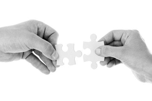 photo représentant deux mains qui assemblent les pièces d'un puzzle pour faire la chasse aux trésors pour enfant.