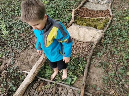 Un enfant marche sur le parcours pieds nus.