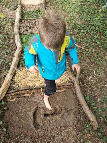 Un enfant marche dans la boue.