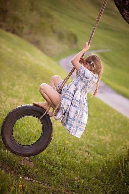 une petite fille se balance pieds nus sur un pneu.