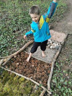 Samuel perd l'équilibre en marchant sur les pomme de pin.