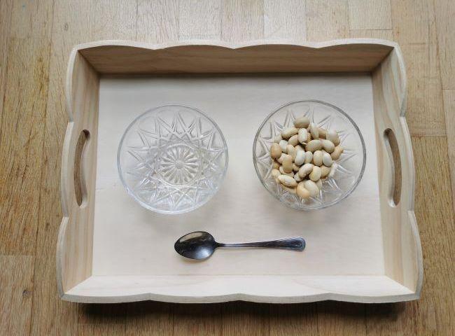 Voici le plateau de vie pratique développé par Maria Montessori: transvaser des graines à la petite cuillère.