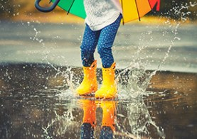young girl in rain puddle
