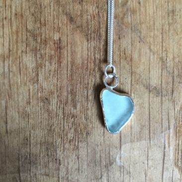 A pale blue piece of seaglass in a heart shape, set in silver to form a necklace