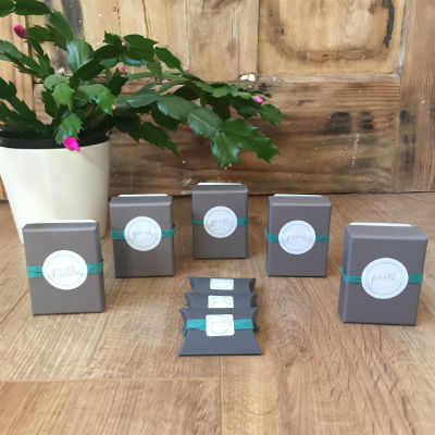 Necklace, ring and earring boxes displayed on a wooden background. Te boxes are grey, sealed with a turquoise strip and the logo sticker