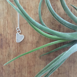Heart-shaped white seaglass necklace set in a silver setting. 2 circular jump rings attach it to the chain.