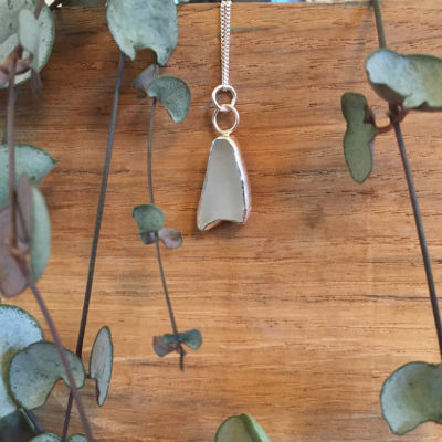 A white seaglass necklace shaped like a mermaids tail with 2 circular jump rings
