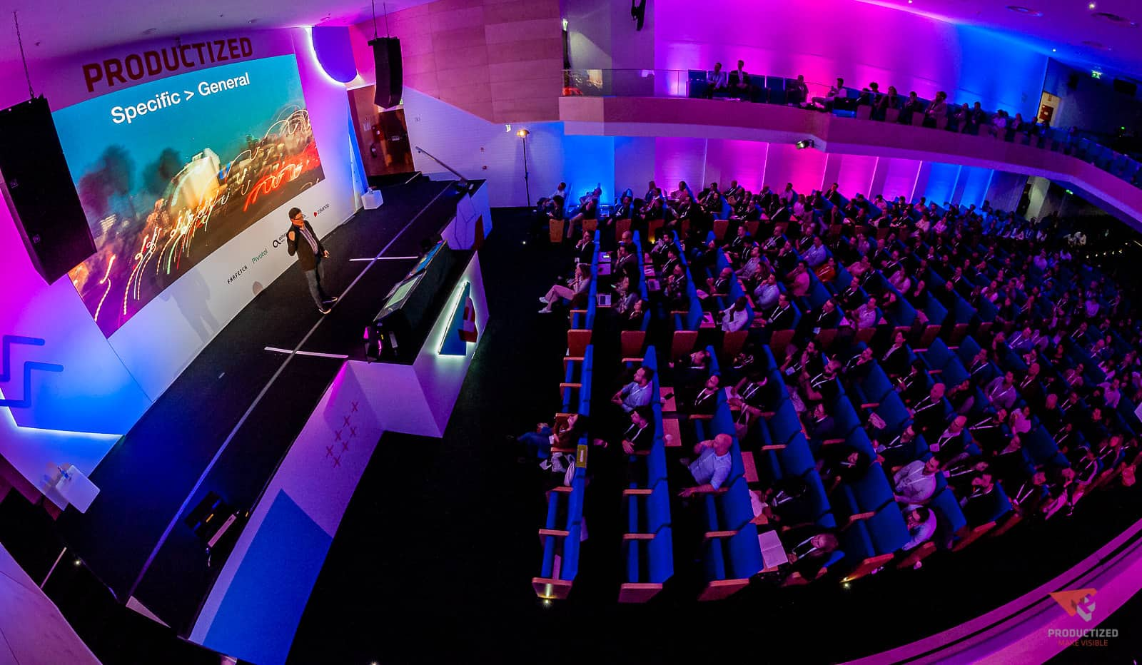the venue and stage of the Productized conference, showing Steve Portigal on stage and the audience