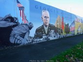 A concrete retaining wall has been covered with murals in remembrance of veterans service.
