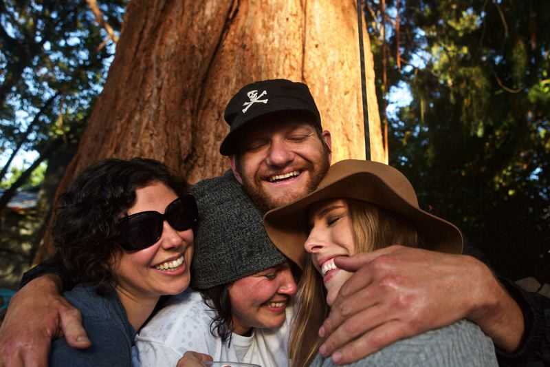 TRIBUNE PHOTO: JAIME VALDEZ - Supporters of Dave Walters embrace him after he rappelled down a sequoia where he spent four days in protest. The tree was part of a stand of three trees slated to be cut down Monday, Sept. 12, leading to a week-long stand-off between protesters, law enforcement and developers.