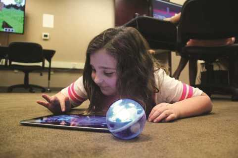 CONNECTION PHOTO: KELSEY O'HALLORAN - McKenna Mitchell, a third-grader at Montclair Elementary School, enjoys driving the 'Sphero' robotic ball using a tablet app at the Fidgets2Widgets after-school enrichment program in Tigard.
