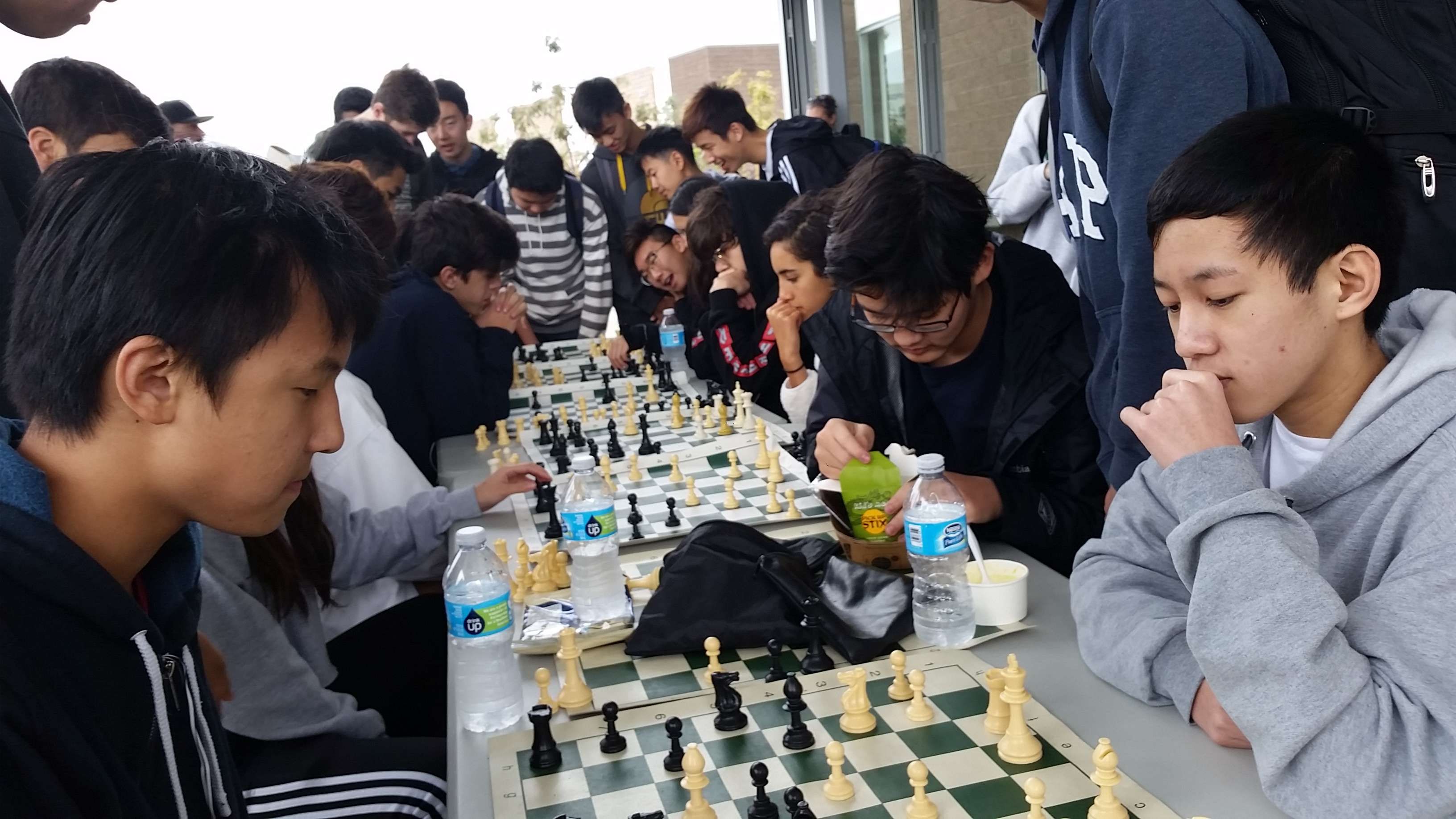 Students gather around chess boards at lunch to play chess with their friends.