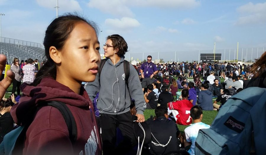 Sophomore Chris Choung lines up with other students on the field as teachers call role during the ShakeOut drill.