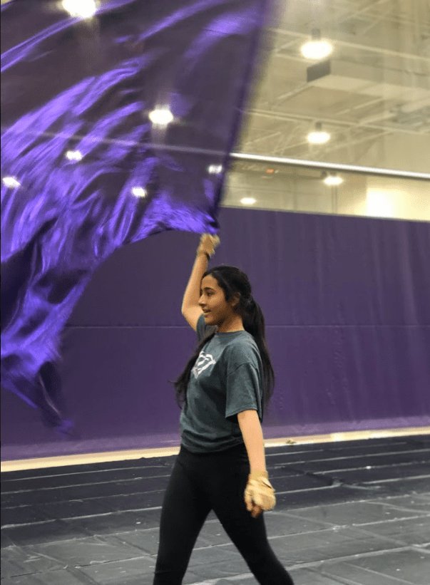 Freshman Mahum Khan flourishes her swing flag to the side before starting her drill during winter guard practice.