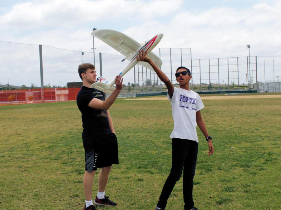 Mike Nassif shows Nick Medvedev how to launch a remote controlled airplane.