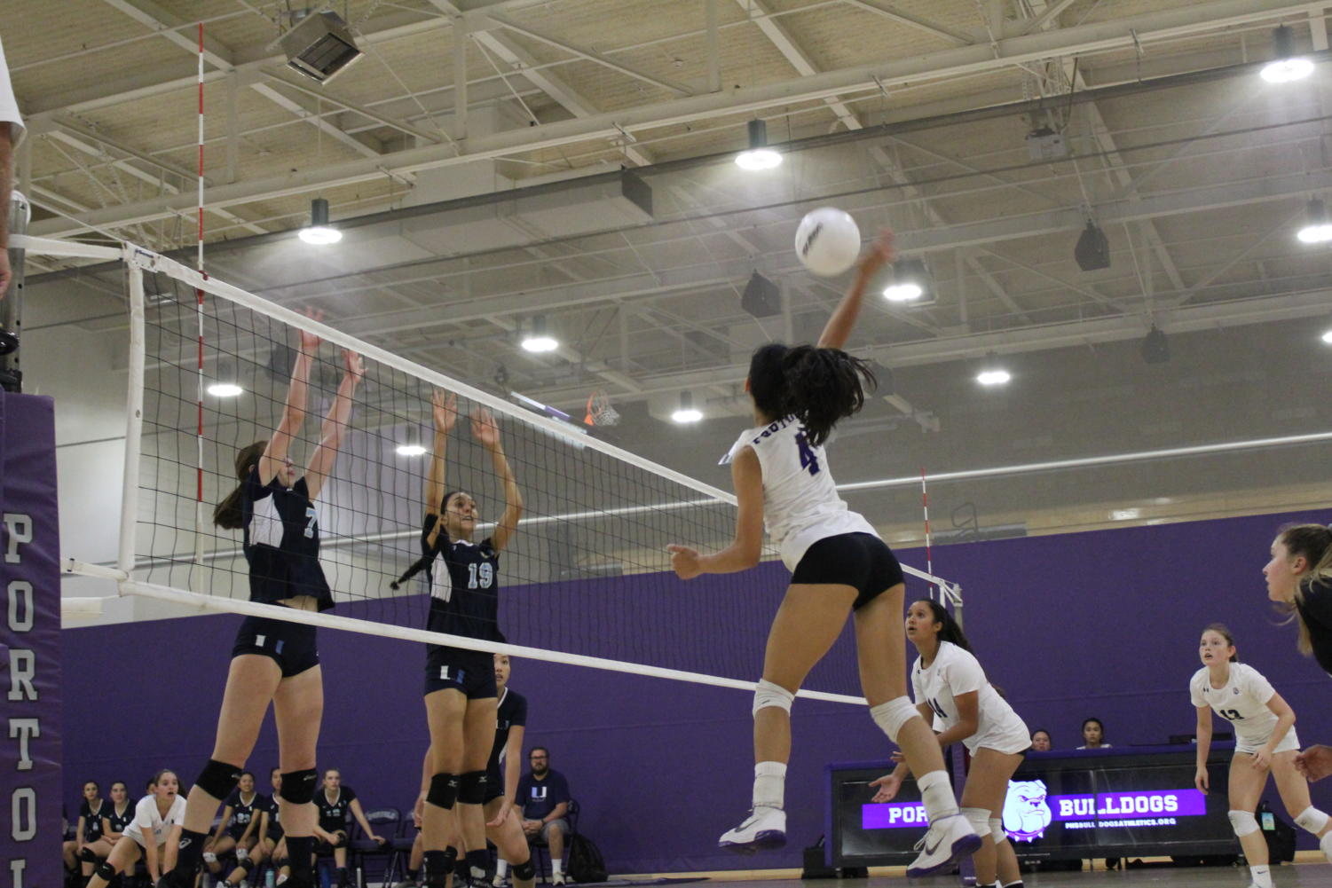 Sophomore Kamdyn Tenorio spikes the ball at the Trojans during the fourth period of the game.