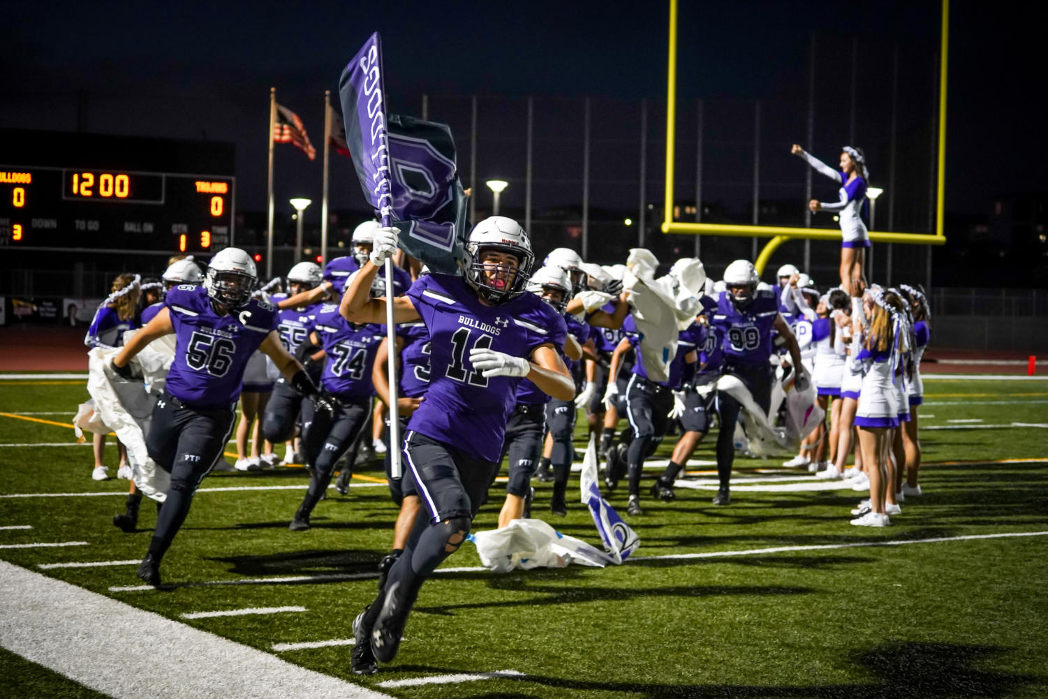 Captain and junior Kaveh Wojtowich leads the football team onto the field before the Forthcoming Game against University