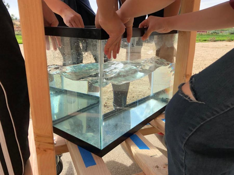 Students+from+the+2017-18+Living+Earth+classes+collaborate+around+a+fish+tank+resting+upon+a+wooden+structure+that+they+constructed+themselves.+The+structure+contains+wheels+that+students+drilled+on+with+help+from+principal+John+Pehrson+in+the+Innovation+Lab.+