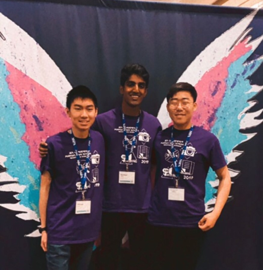 Juniors William Hsieh, Rane, and Ki Joon lee (left to right) pose in front of a painted mural at the convention.