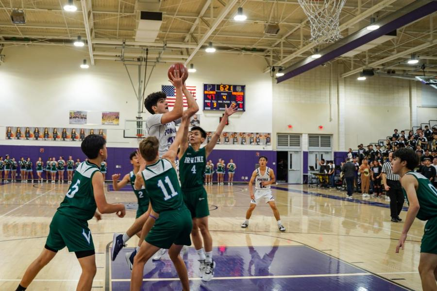 Forward and senior Mohsen Hashemi flies to rim while contested by Irvine High players. Hashemi was the Bulldogs' leading scorer with 21 points.