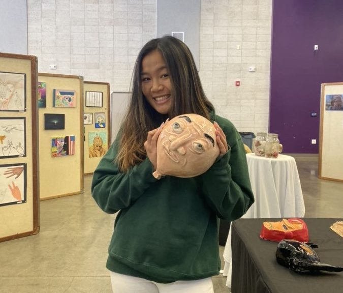 """Junior Kayla Nguyen presents her ceramics creation of """"Balloony,"""" inspired by the television show """"Phineas and Ferb,"""" at Fine Arts Week."""