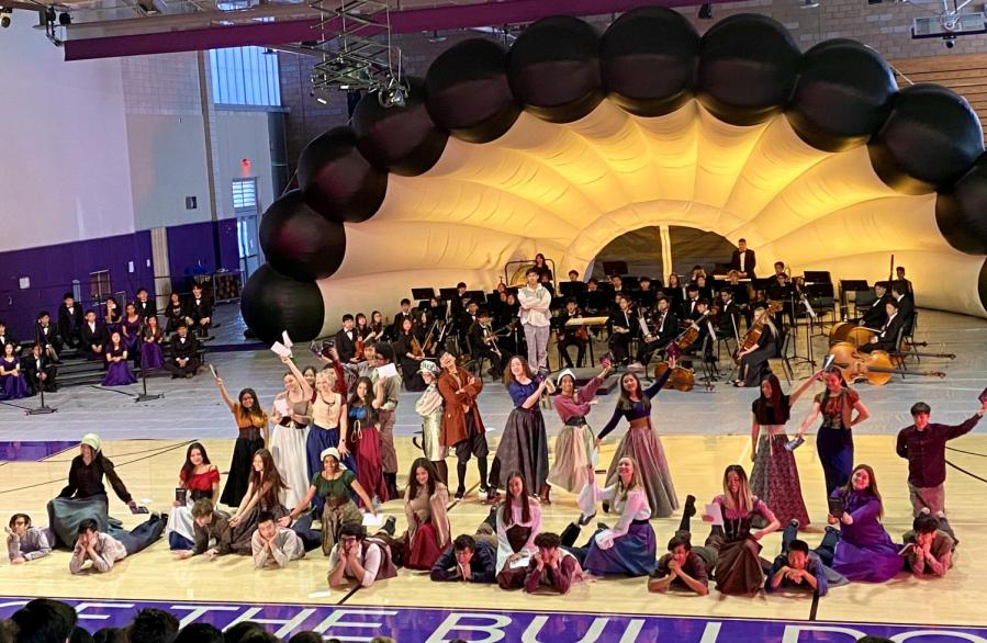 """From townsfolk to aristocrats, the cast of Cinderella gathers before the student body for the big finish during the teaser performance of """"The Prince is Giving a Ball"""" for the annual Fine Arts Assembly."""
