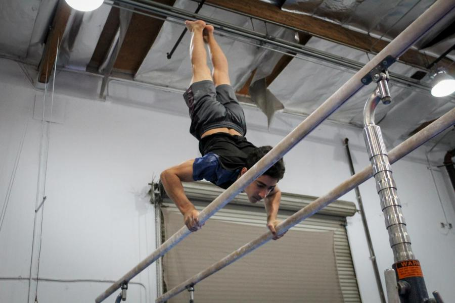 Sophomore Kian Miremadi maintains a handstand during his swing on parallel bars. The drill combines aspects of strength and balance, requiring the gymnast to have upper-body control.