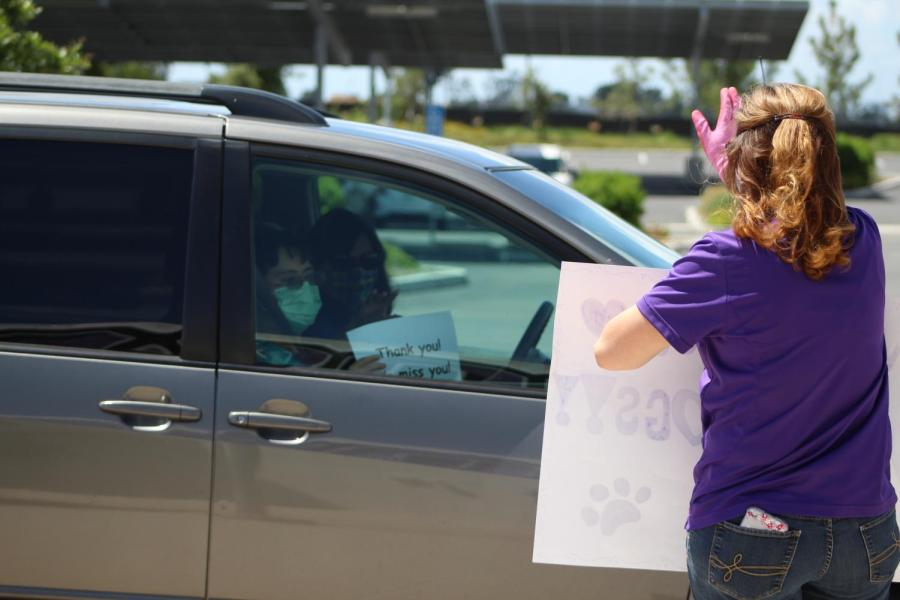 """Education specialist Desiree Shaffer waves a """"Go Bulldogs"""" sign to incoming cars of students and family members, who show their appreciation even behind windows and masks. From a safe distance, Shaffer stops to check in and chat with the families before sending them down the line of other cheerful staff members."""