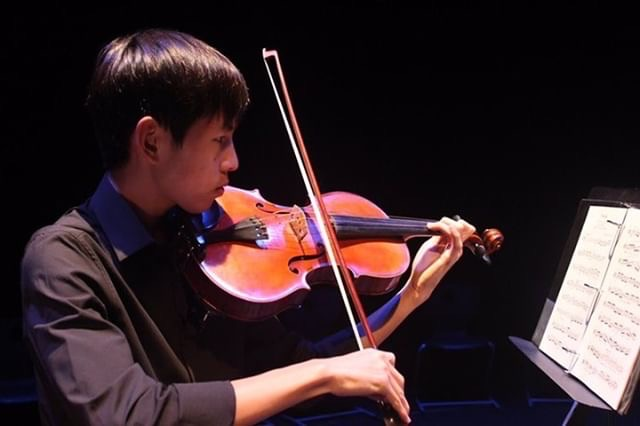 """Senior Wesley Tjangnaka practices his viola to prepare for his solo performance in """"October."""" Because he is performing for both Concert and Symphonic Orchestra, he has more pieces to practice than others."""