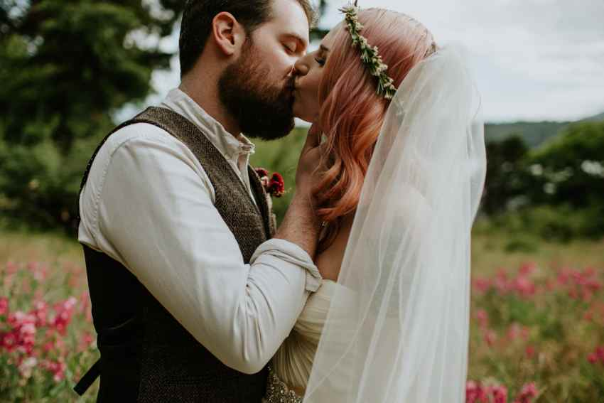 groom kissing bride with pink hair