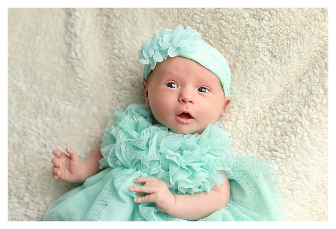 newborn photo studio picture with girl in teal dress