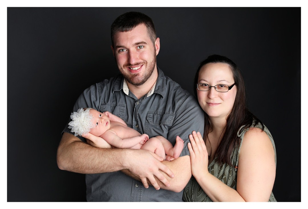 newborn with parents in studio session