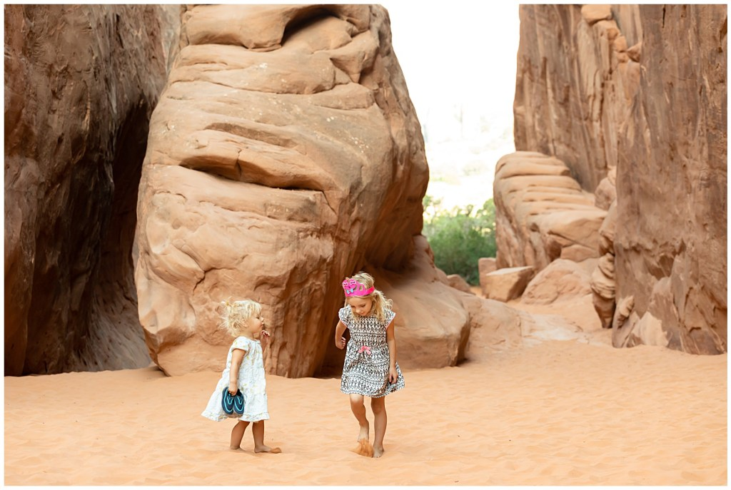 girls in sand at arches national park