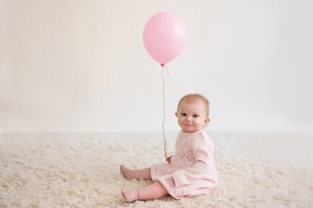 girl sitting with pink balloon